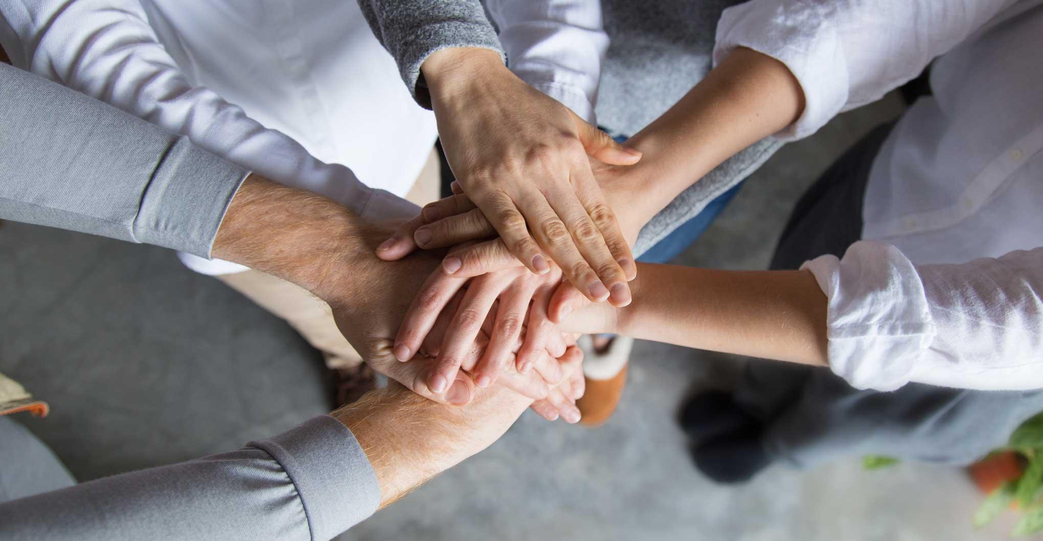 Manos de los integrantes de The Canvas Group reunidas para fortalecer el trabajo en equipo y la cultura agil